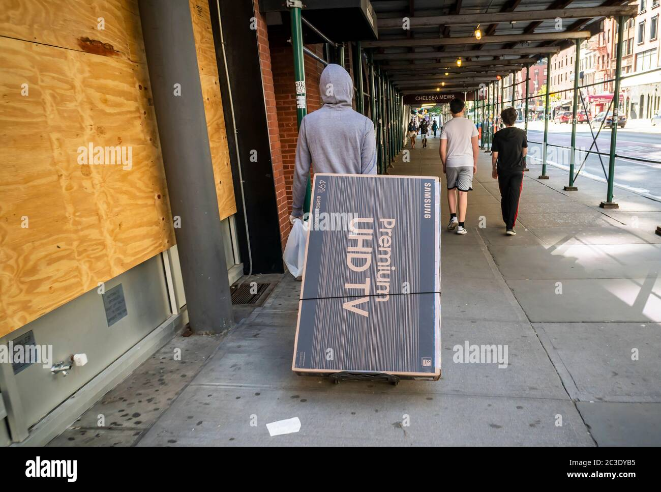 Customer carries his Samsung brand flat-screen television in Chelsea in New York on Saturday, June 13, 2020 as  stores open for curbside pick-up during Phase One of the city's reopening.  (© Richard B. Levine) Stock Photo