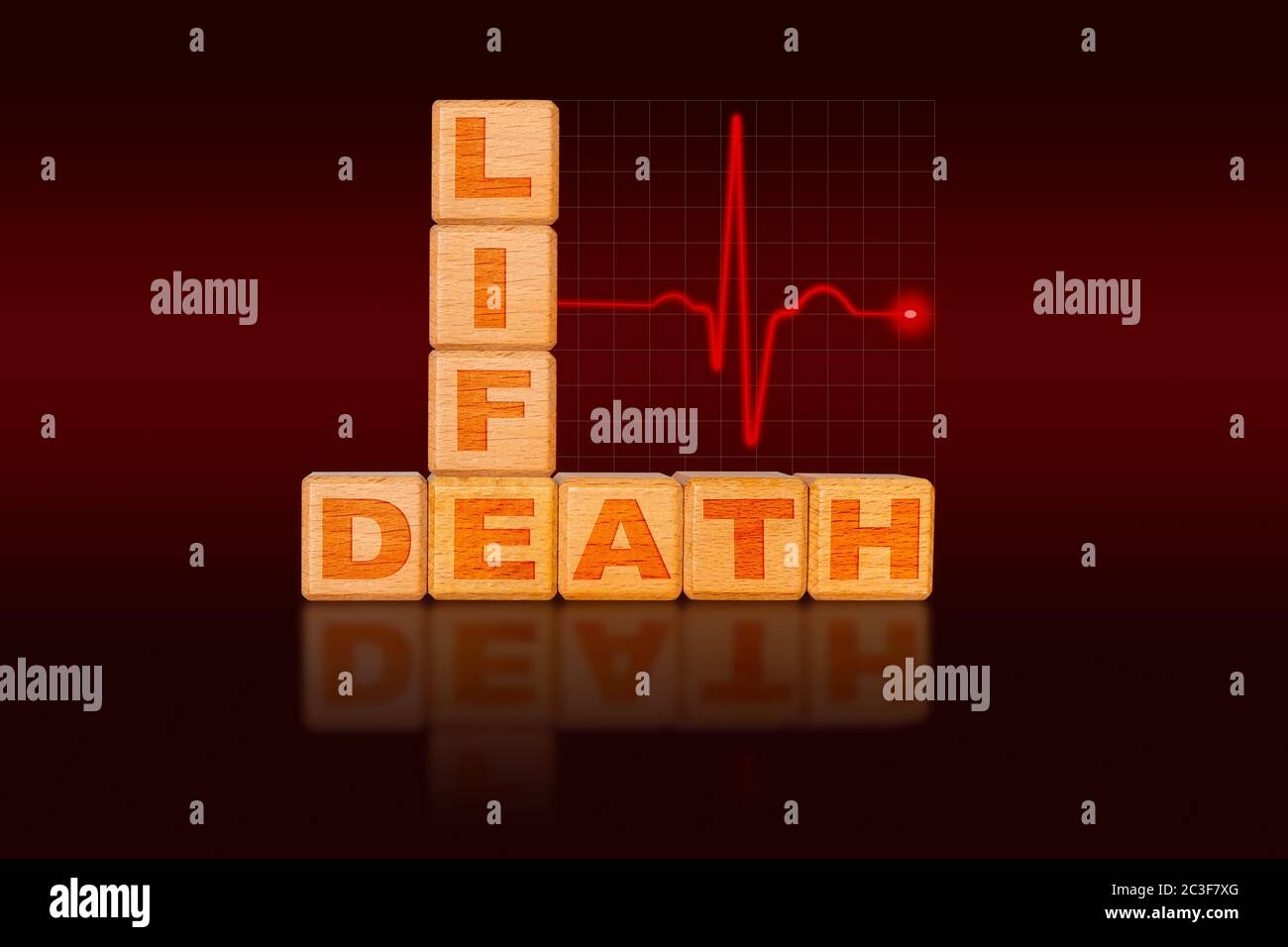life and death concept written on alphabet blocks in the form of a chart with ecg electrocardiogram showing strong heart beat initially followed by fl 2C3F7XG