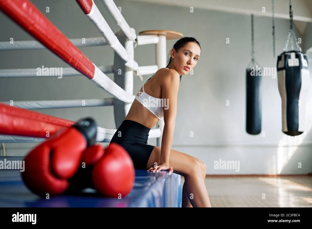 Young beautiful woman relax after fight or workout exercising in boxing ring Stock Photo