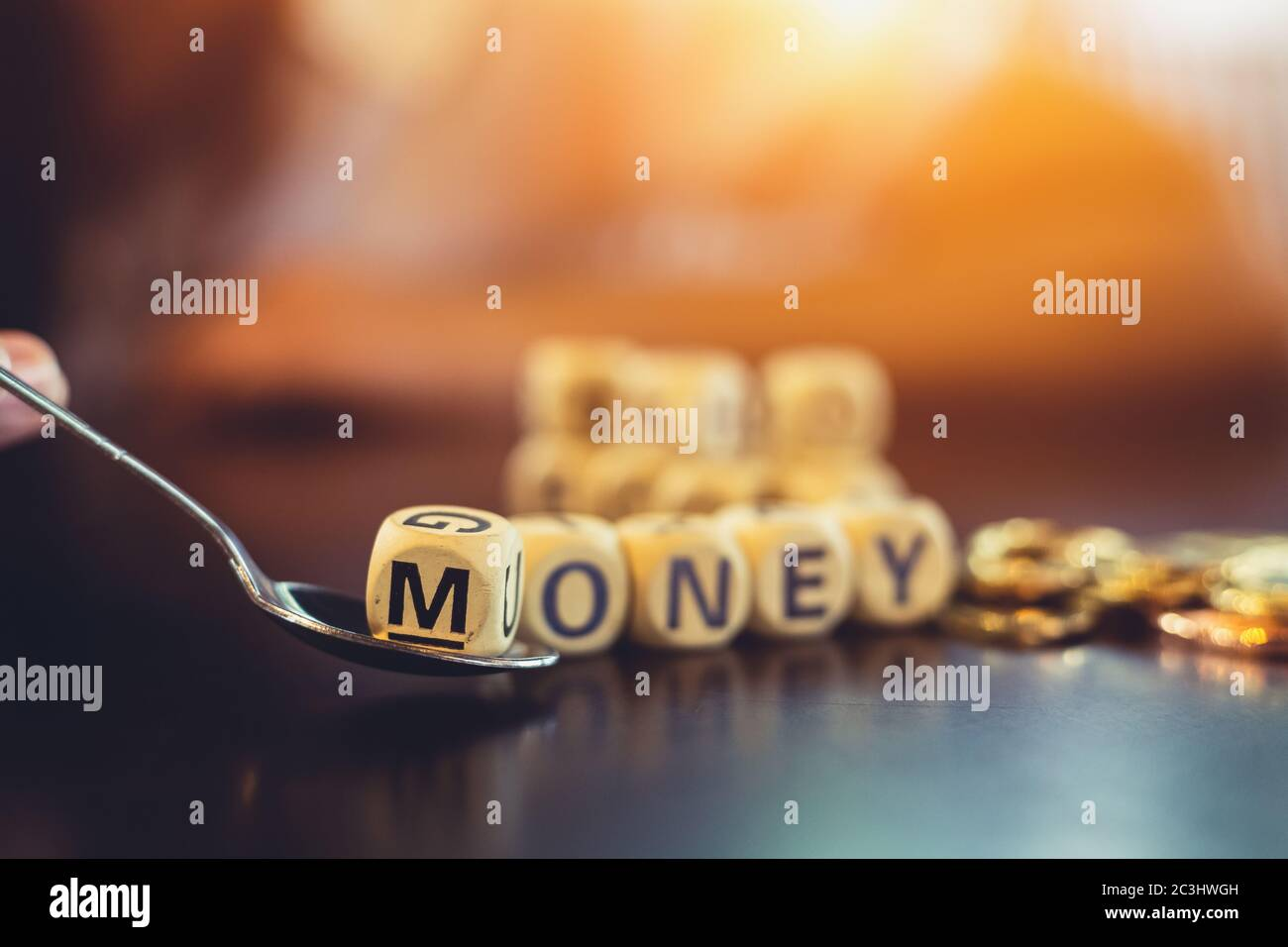 """wood cube word """"M"""" on spoon. Business payment concept. Stock Photo"""