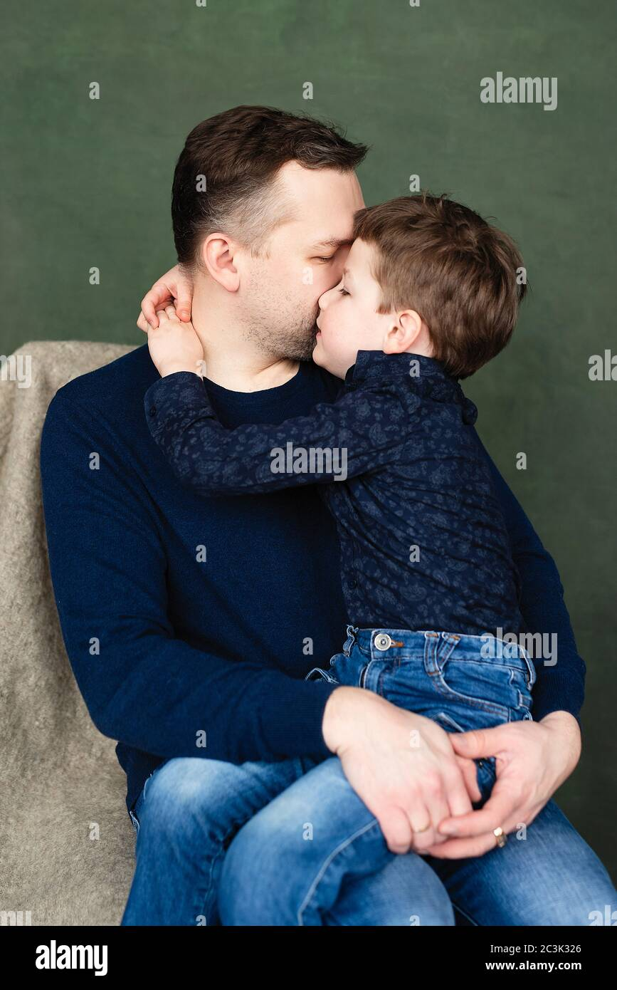 boy hugs and kisses his dad, man holds child in his arms Stock Photo