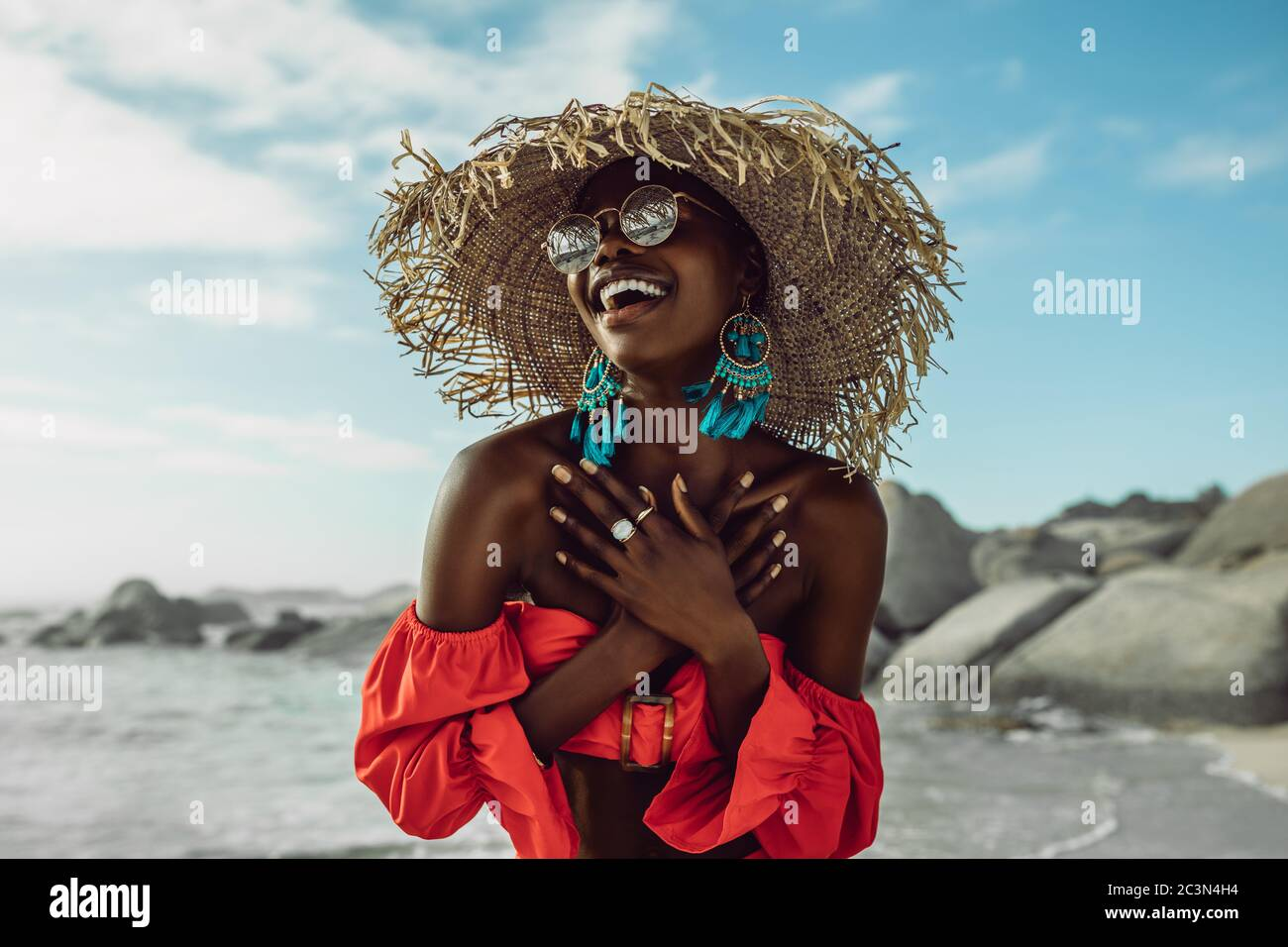 Beautiful african woman in red dress wearing straw hat smiling on the beach. Female in sundress enjoying on the beach. Stock Photo