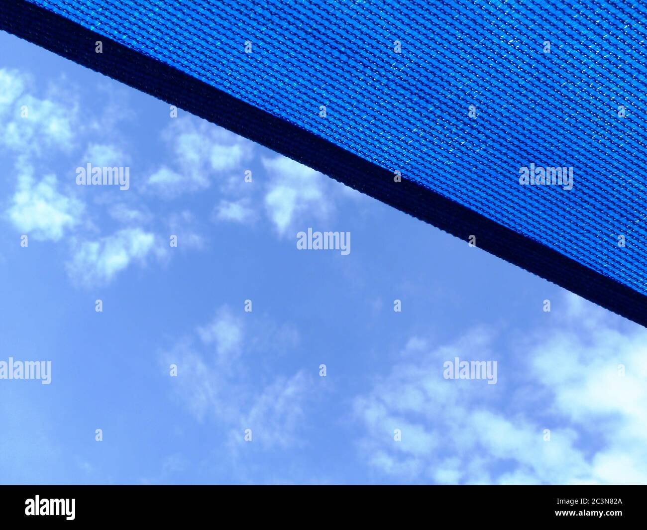 loosely weaved fabric parasol awning. blue sky with clouds. sunny summer day. sun and UV exposure protection concept. medium blue sun proof fabric. Stock Photo