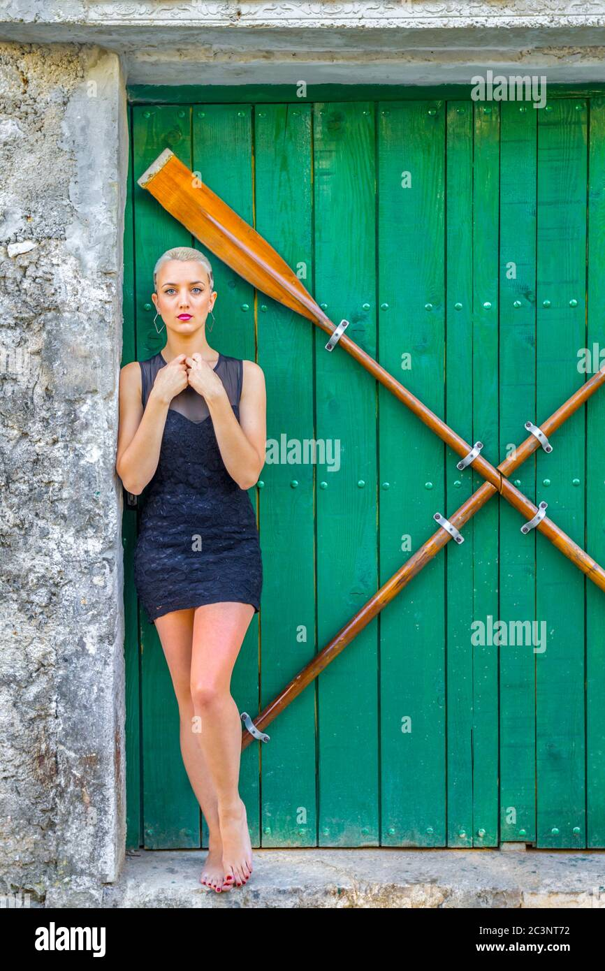Young woman standing barefeet wearing small little Black dress minidress clothing Stock Photo