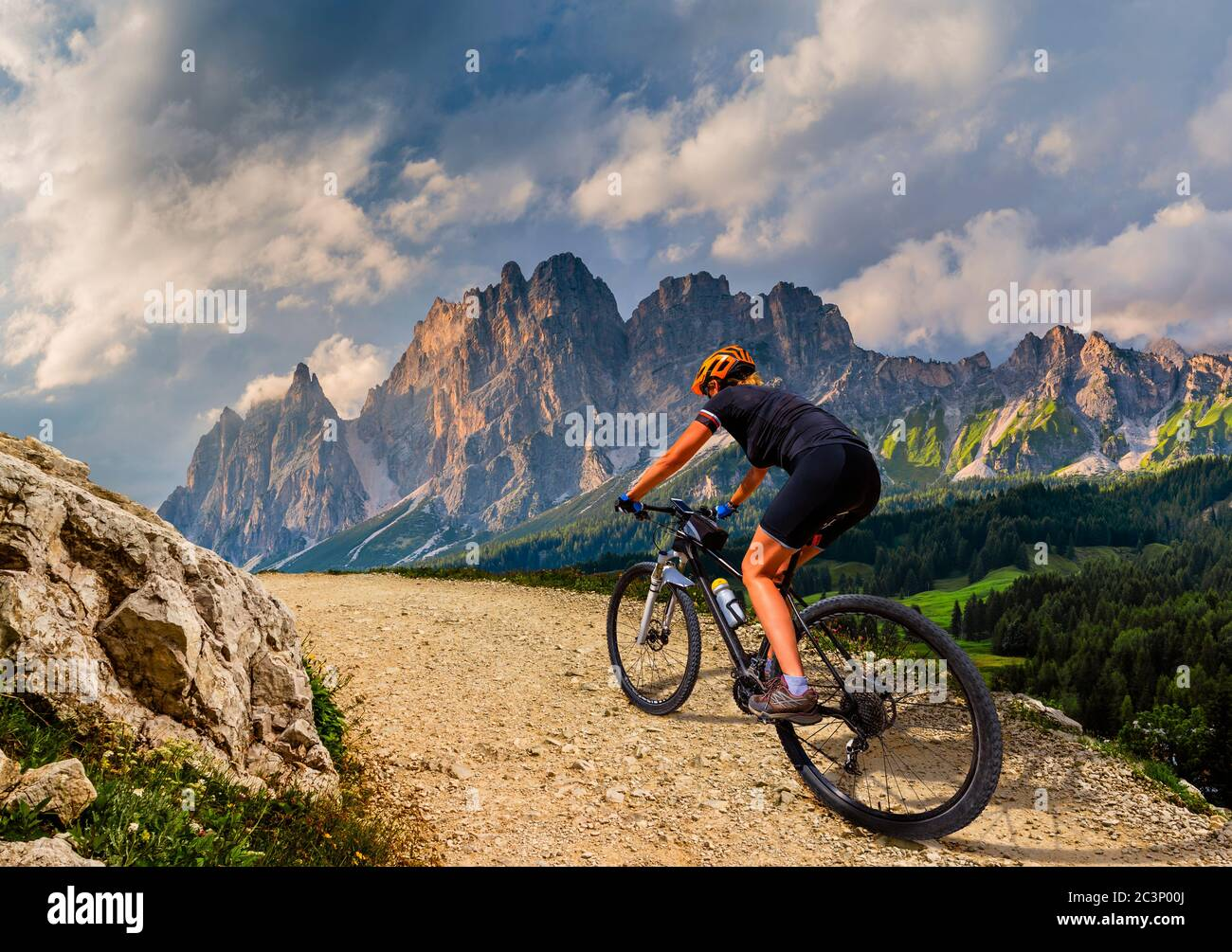 Tourist cycling in Cortina d'Ampezzo, stunning rocky mountains on the background. Woman riding MTB enduro flow trail. South Tyrol province of Italy, D Stock Photo