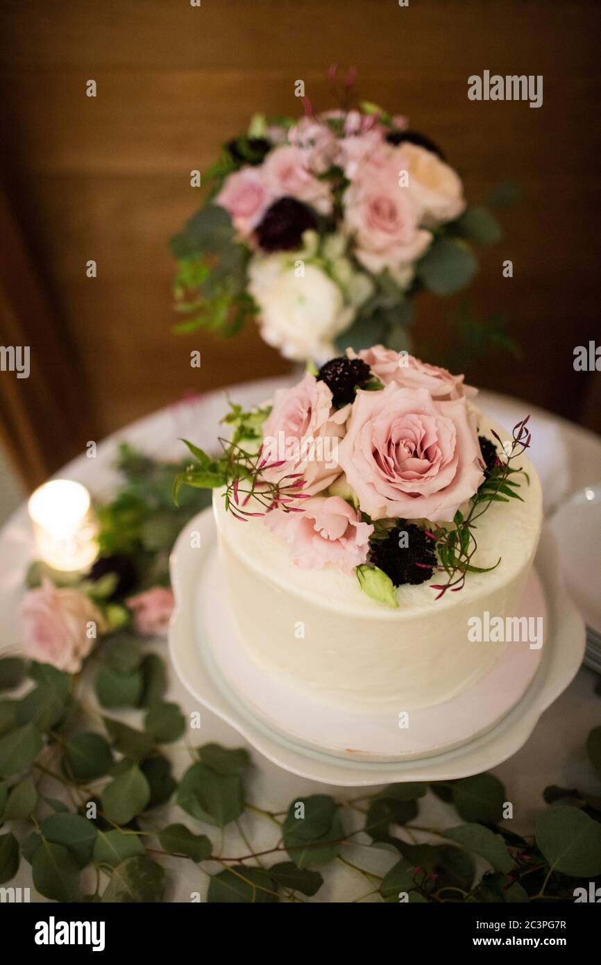 A Vertical Shot Of A Cake With Flower Decorations On A Tray On The Table Under The Lights Stock Photo Alamy