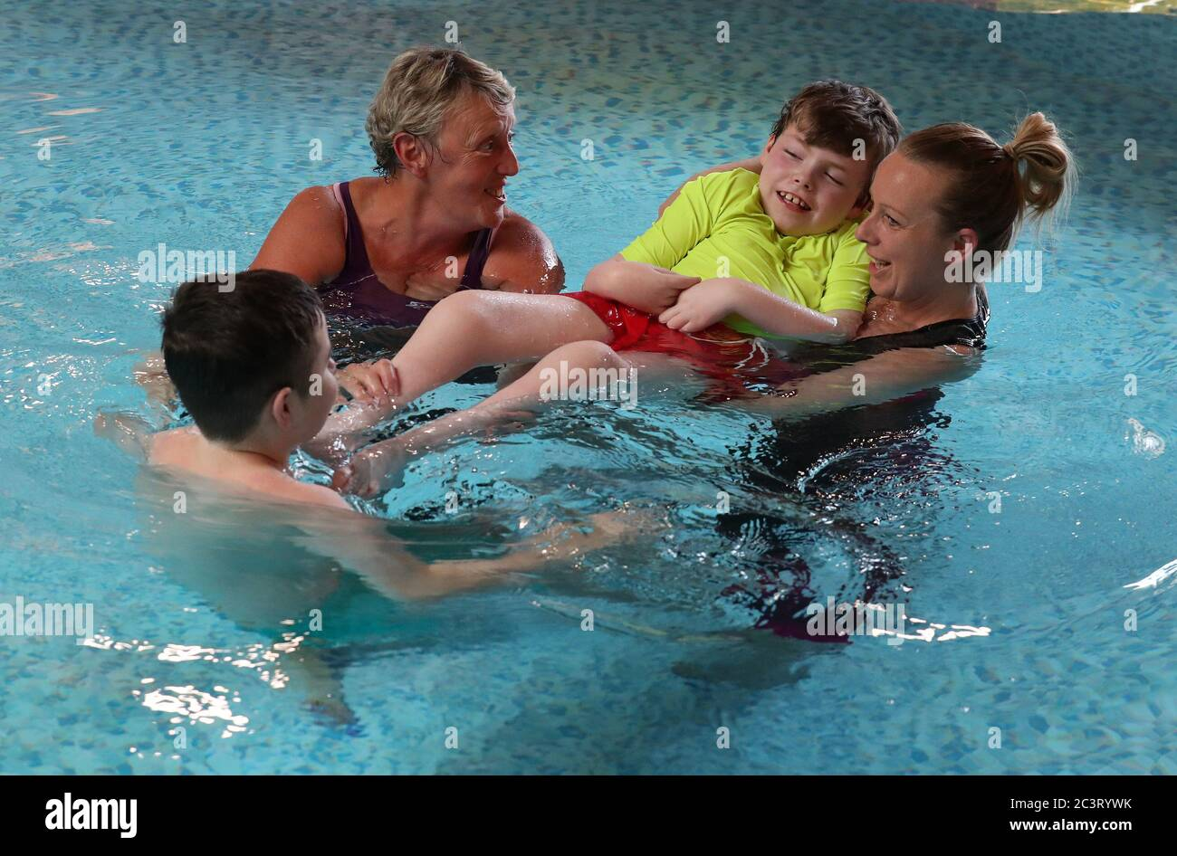 Early Years Practitoner Carole King (left) alongside Nicola Devlin with her sons Sean Kearns and Evan (back to camera) as they take part in Parent-led aquatic therapy in the Hydrotherapy pool at the Craighalbert Centre. Coronavirus adaptations have been installed at the Scottish Centre for Children with Motor Impairments, Craighalbert Centre, Cumbernauld, as Scotland continues gradually lifting coronavirus lockdown measures. Stock Photo