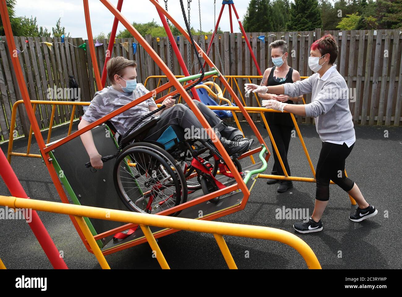 Gregor Marshall with his mum Karen alongside Early Years Practitioner Catherine Anderson (right) as Gregor has a ride on the wheelchair swing in the outside therapy area at the Craighalbert Centre. Coronavirus adaptations have been installed at the Scottish Centre for Children with Motor Impairments, Craighalbert Centre, Cumbernauld, as Scotland continues gradually lifting coronavirus lockdown measures. Stock Photo