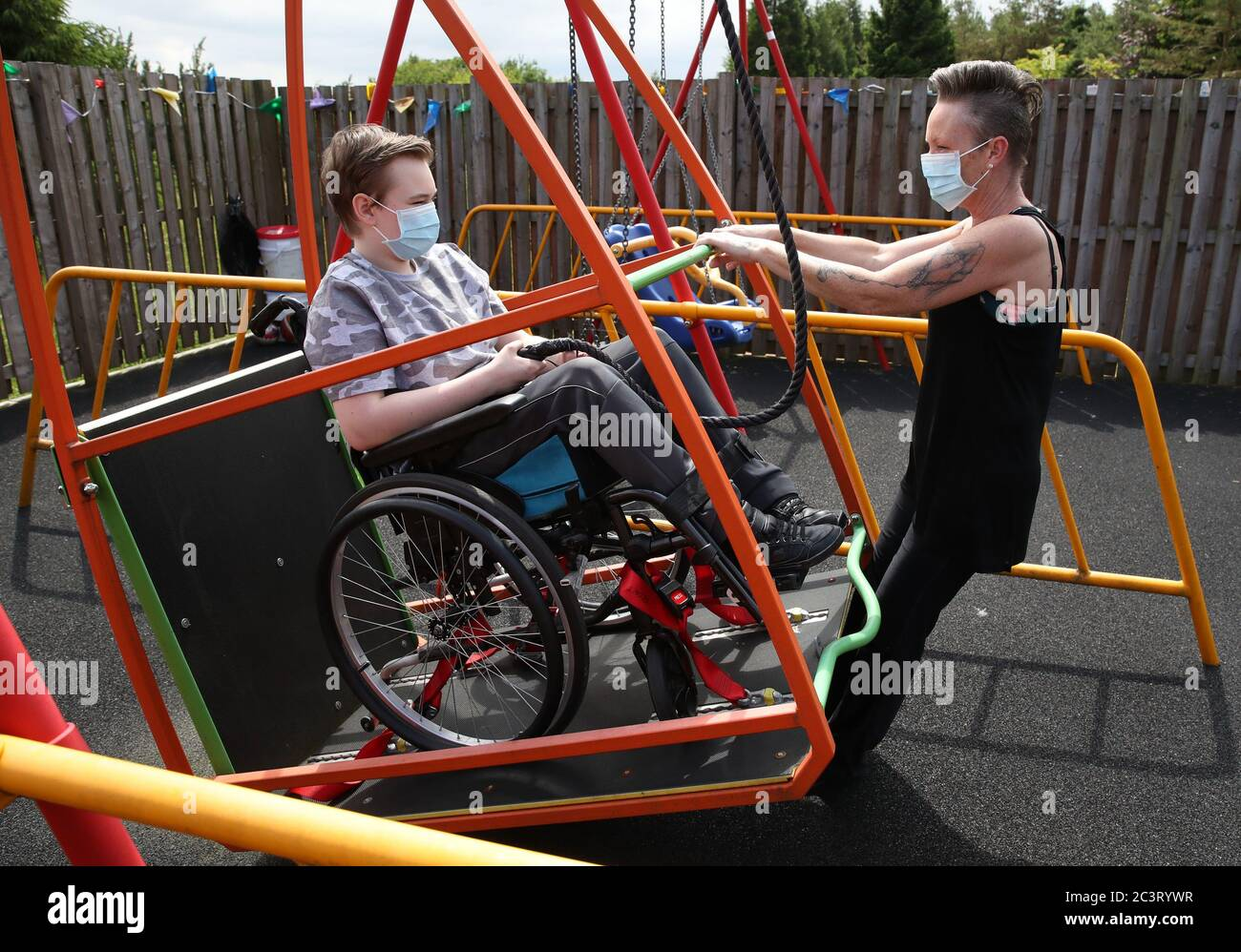 Gregor Marshall with his mum Karen as Gregor has a ride on the wheelchair swing in the outside therapy area at the Craighalbert Centre. Coronavirus adaptations have been installed at the Scottish Centre for Children with Motor Impairments, Craighalbert Centre, Cumbernauld, as Scotland continues gradually lifting coronavirus lockdown measures. Stock Photo