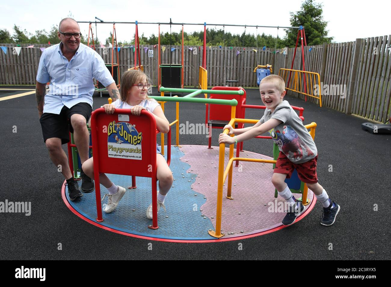 Callum McMichael pushes his sister Laura and father Barry on the roundabout in the outside therapy area at the Craighalbert Centre. Coronavirus adaptations have been installed at the Scottish Centre for Children with Motor Impairments, Craighalbert Centre, Cumbernauld, as Scotland continues gradually lifting coronavirus lockdown measures. Stock Photo