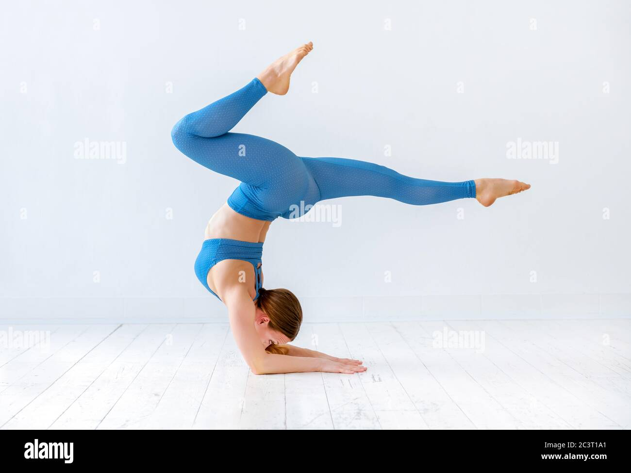 Athletic woman doing an elbow stand yoga pose with outstretched ...