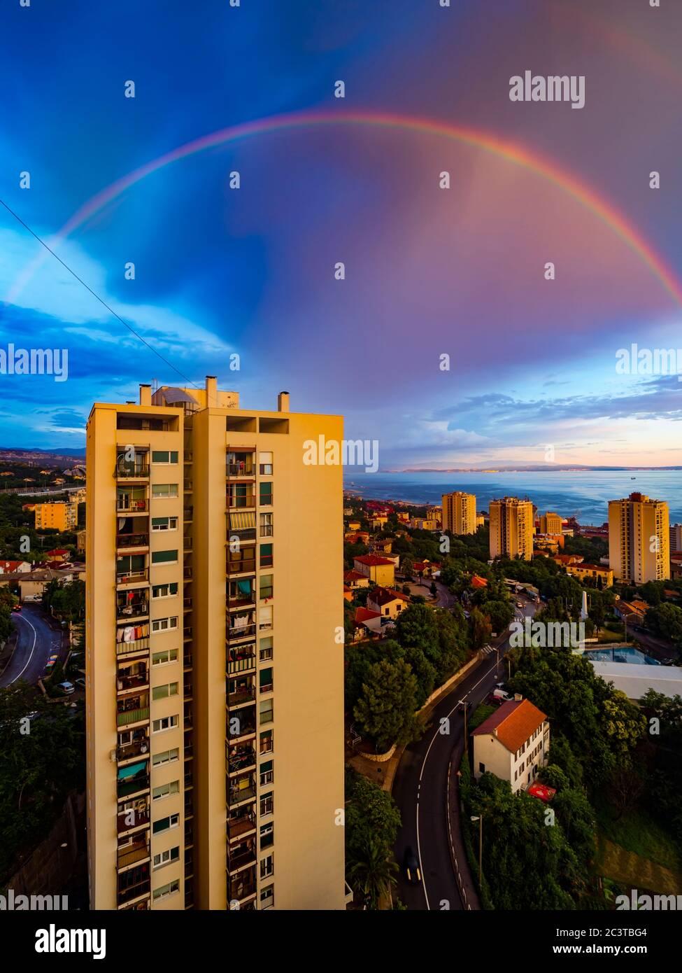 Evening full arc arch rainbow above skyscraper house building Stock Photo