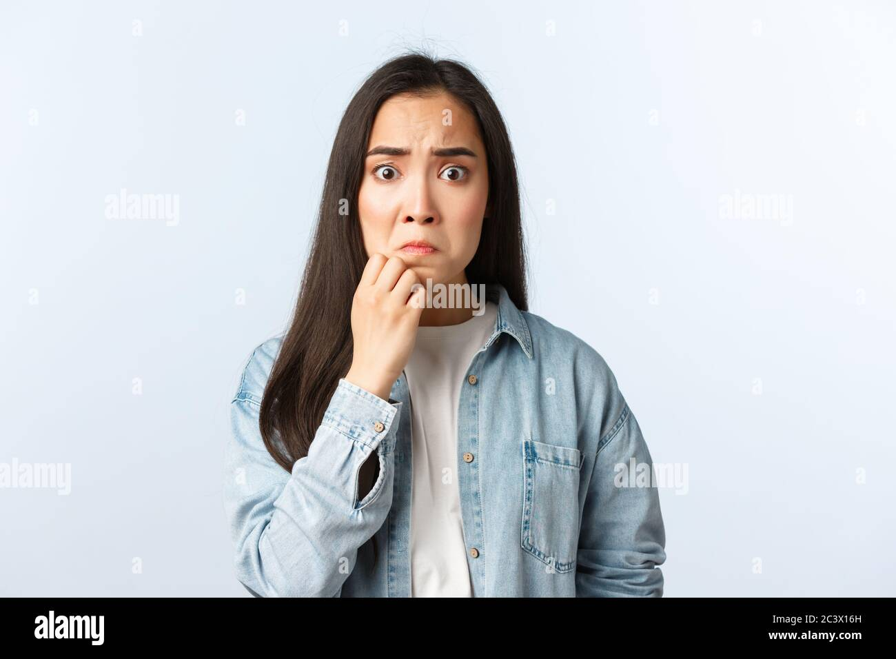 Lifestyle, people emotions and beauty concept. Anxious and concerned panicking asian girl grimacing, touching chin, look guilty or nervous, worried Stock Photo