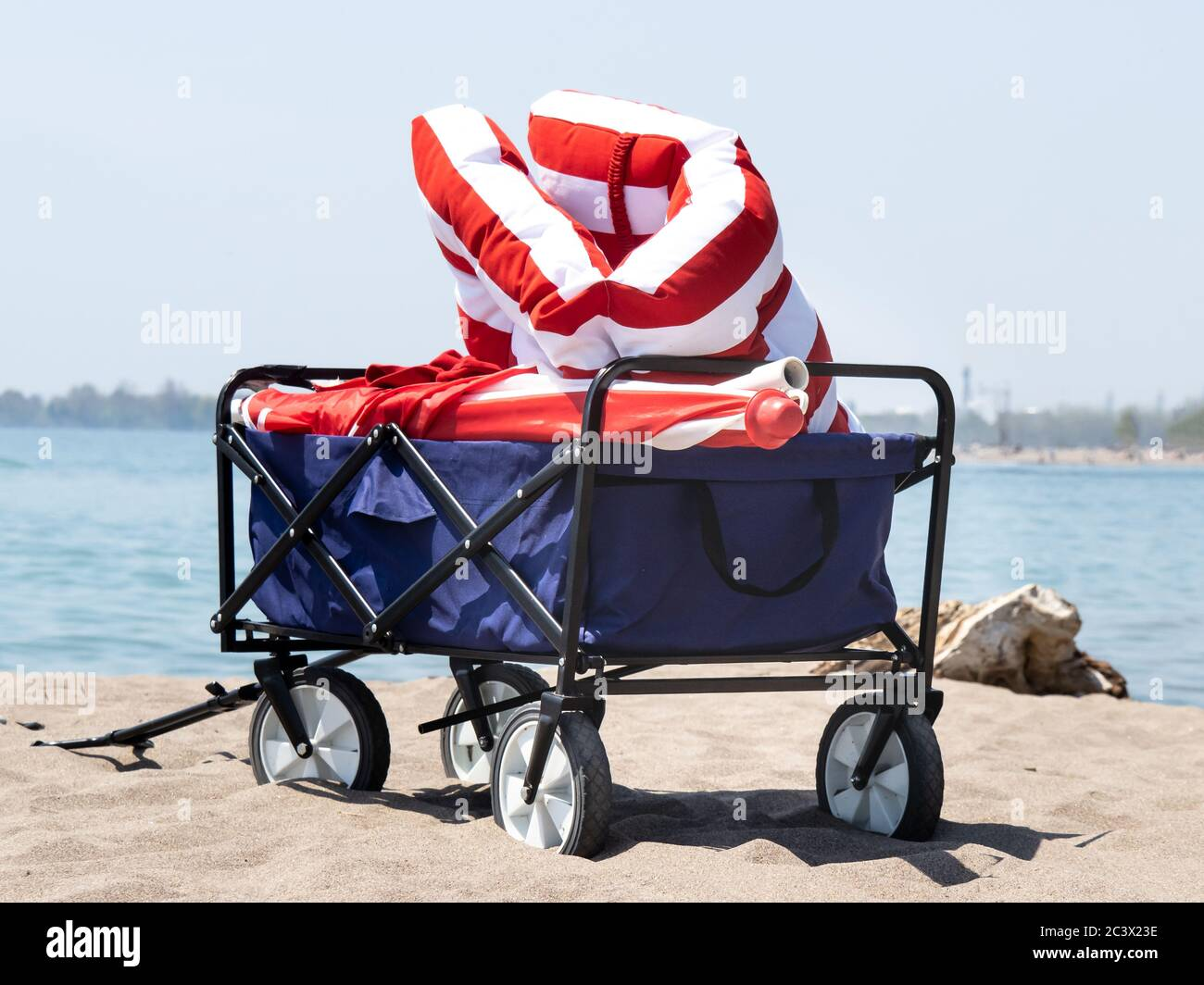 A Folding Beach Wagon On The Sand Filled With Red Cushions And An Umbrella Stock Photo Alamy