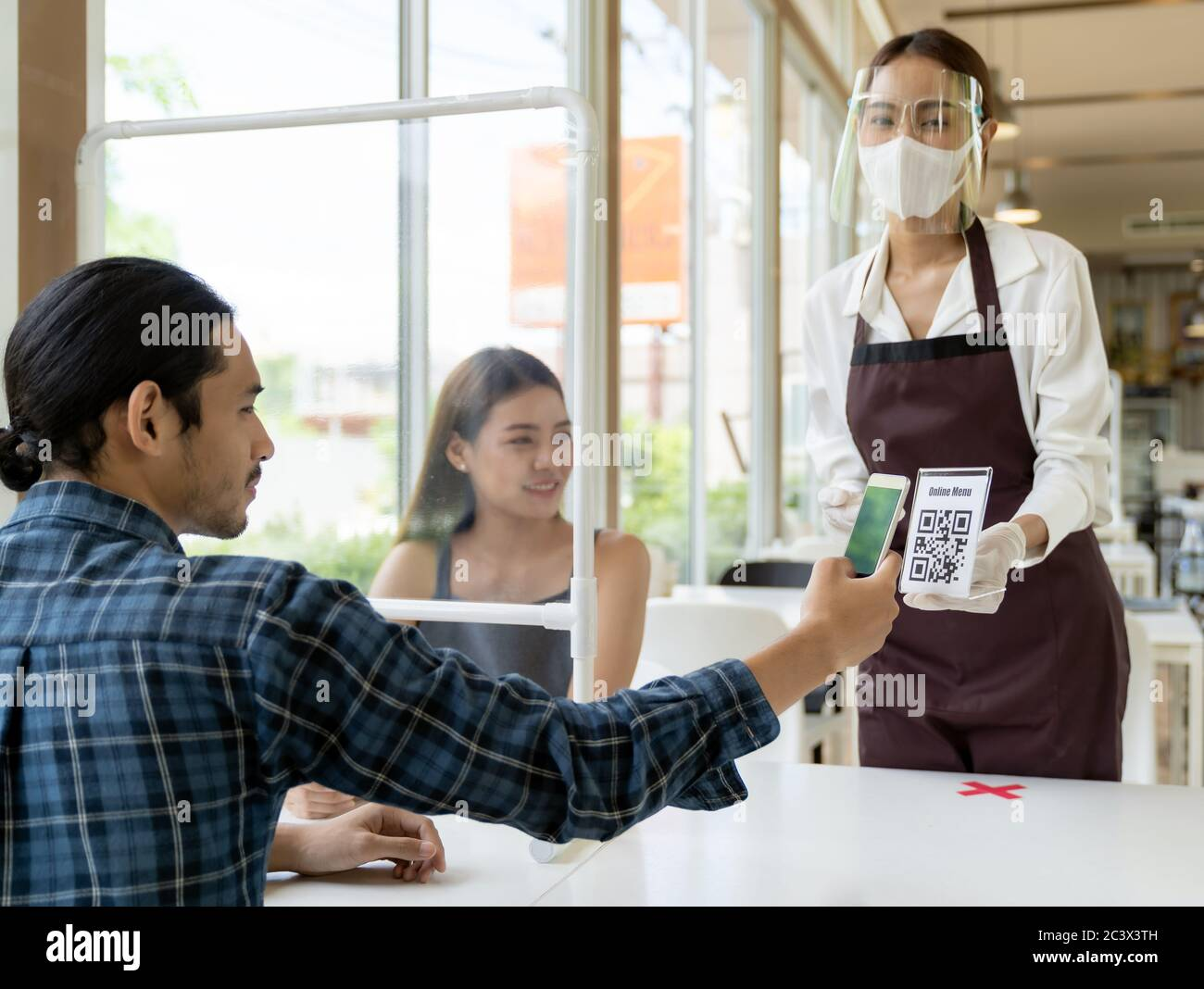 Asian customer scan QR code online menu from waitress with face mask and face shield. Customer sat on social distancing table for new normal lifstyle Stock Photo