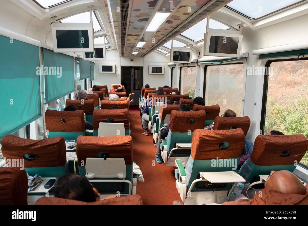 Passengers inside the modern TEJAS EXPRESS train to Goa, India. Stock Photo