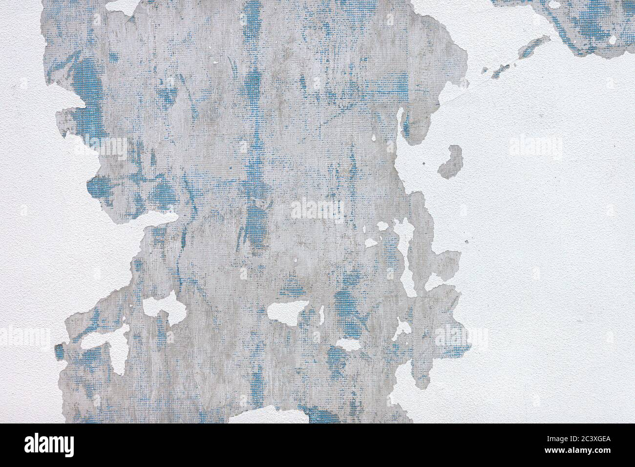White shabby wall surface with peeling plaster and paint. Building facade with damaged paint. Texture, background Stock Photo
