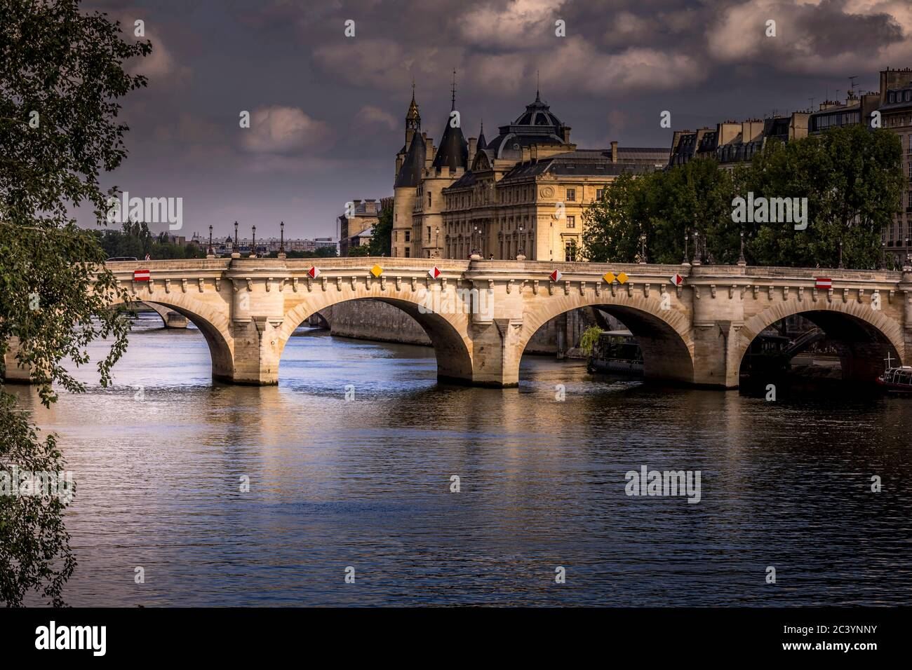 Paris, France - June 9, 2020: Nice view of Pont Neuf bridge and Conciergerie in background on a stormy end of the day in Paris Stock Photo