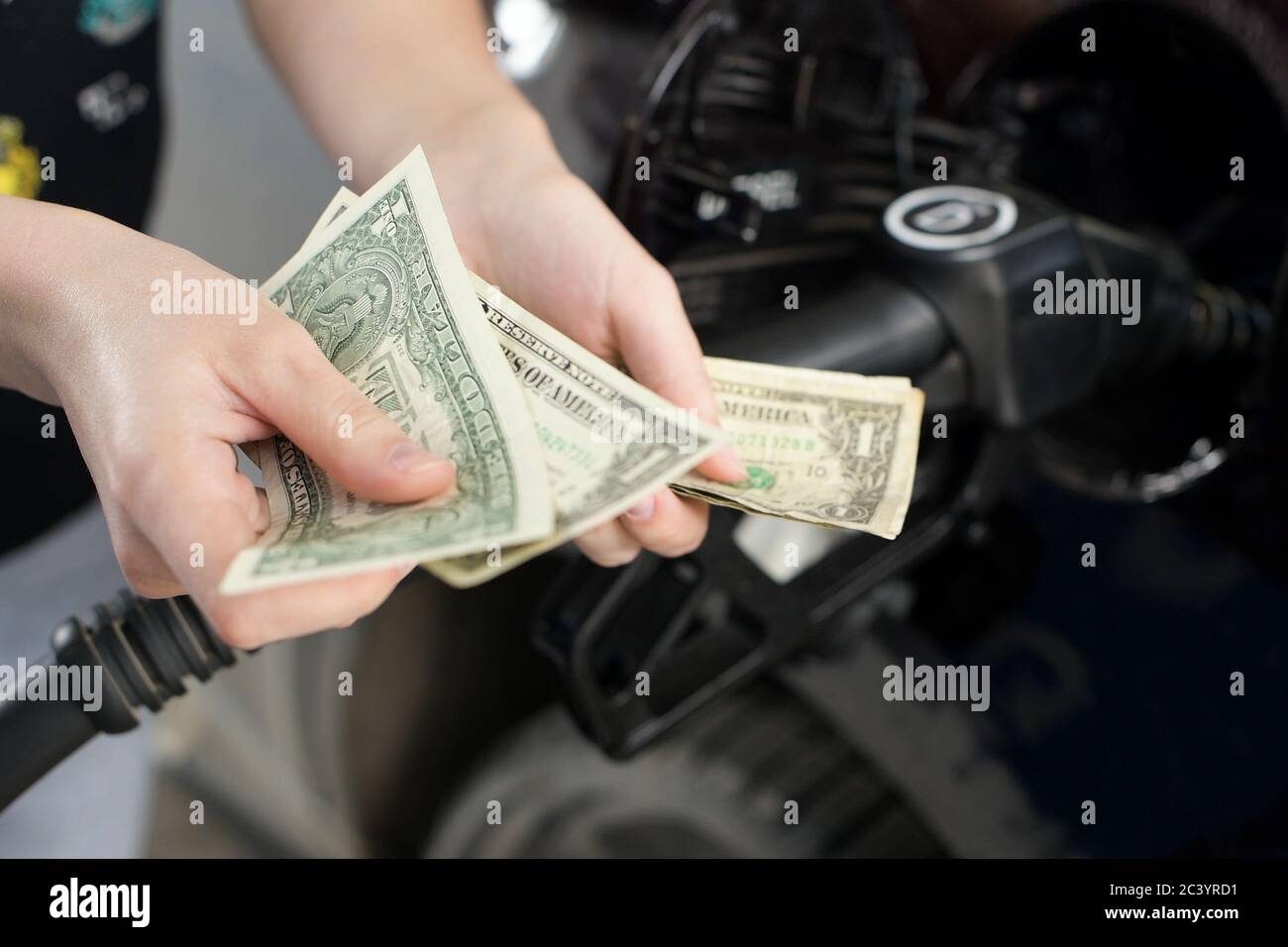 hands counts crumpled dollar bills against the background of fueling car Stock Photo
