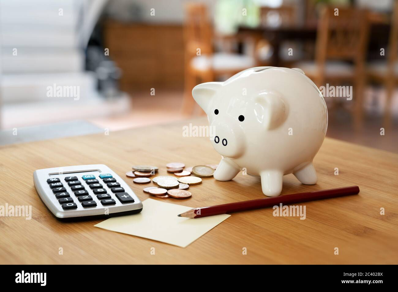 Economy concept, calculator with coins, pencil and a piggy bank on a table in the living room, calculating finances and saving household money, copy s Stock Photo