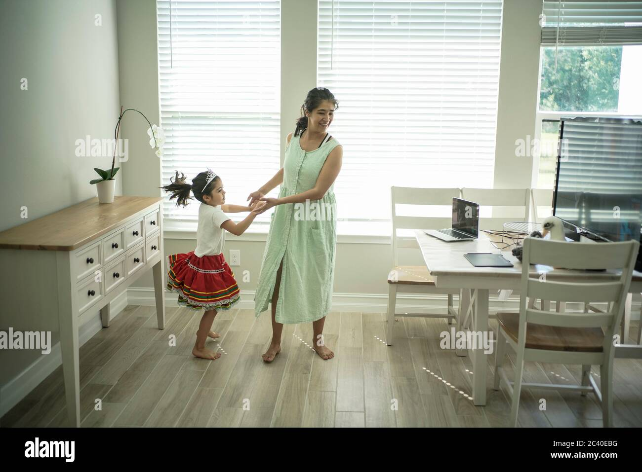Girl enjoys an online dance class with a laptop connected to a TV at home Stock Photo