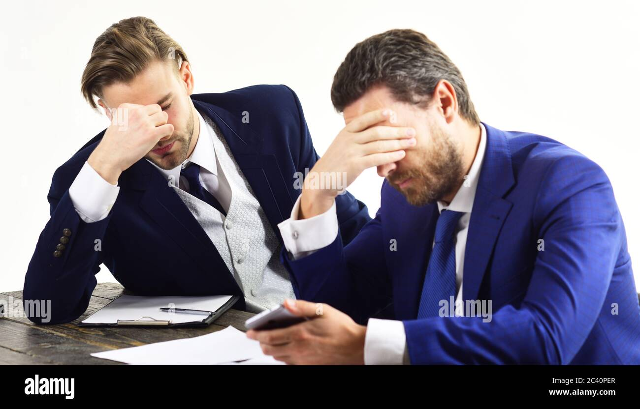 Men in with tired, worried faces read about business fail. Partners in formal suits look at smartphone. Bad luck, lack of money, company failure. Domino effect and failed business concept. Stock Photo