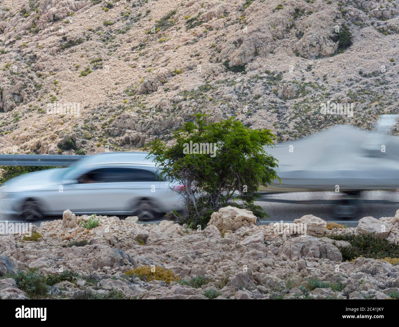 White car vehicle with trailing trailer carrying boat passing by intentionally blurry conveying speed Stock Photo
