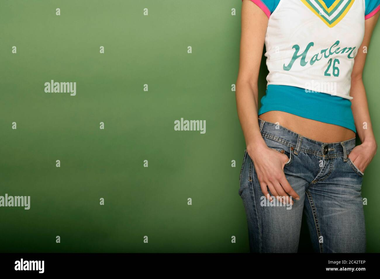 Young woman in a modern t-shirt leans against a wall - cutout - trend - youth Stock Photo