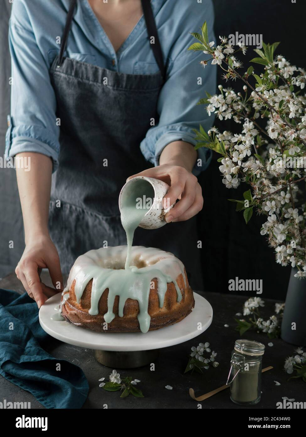 Young Woman In Blue Shirt And Gray Apron Pouring Green Matcha Glaze On Bundt Cake On Dark Background Bunt Cake On Marble Cake Stand And Green Tae Mat Stock Photo Alamy