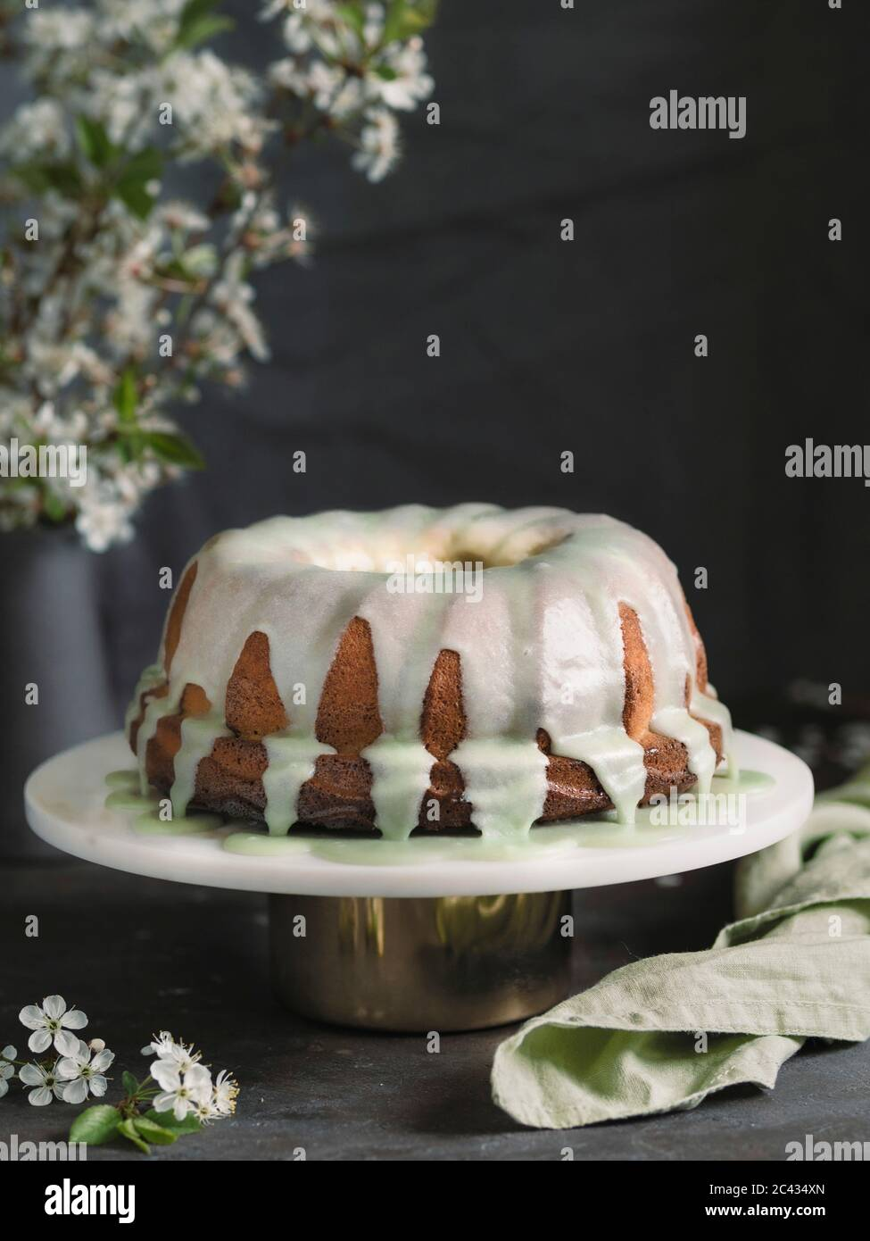 Bundt Cake With Green Matcha Glaze On White Marble Cake Stand Over Dark Table With Bouquet Of Blossoming Cherry Or Pear Branches Copy Space Top Over Stock Photo Alamy