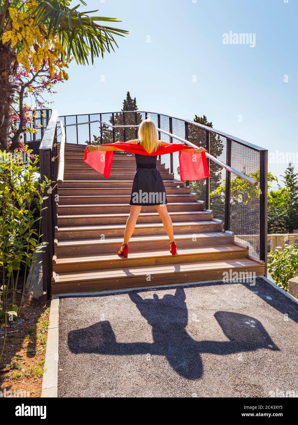 Attractive blonde woman standing spreading apart hands arms legs holding hold bright Red scarf against light sunlight sunshine on staircase MR Stock Photo