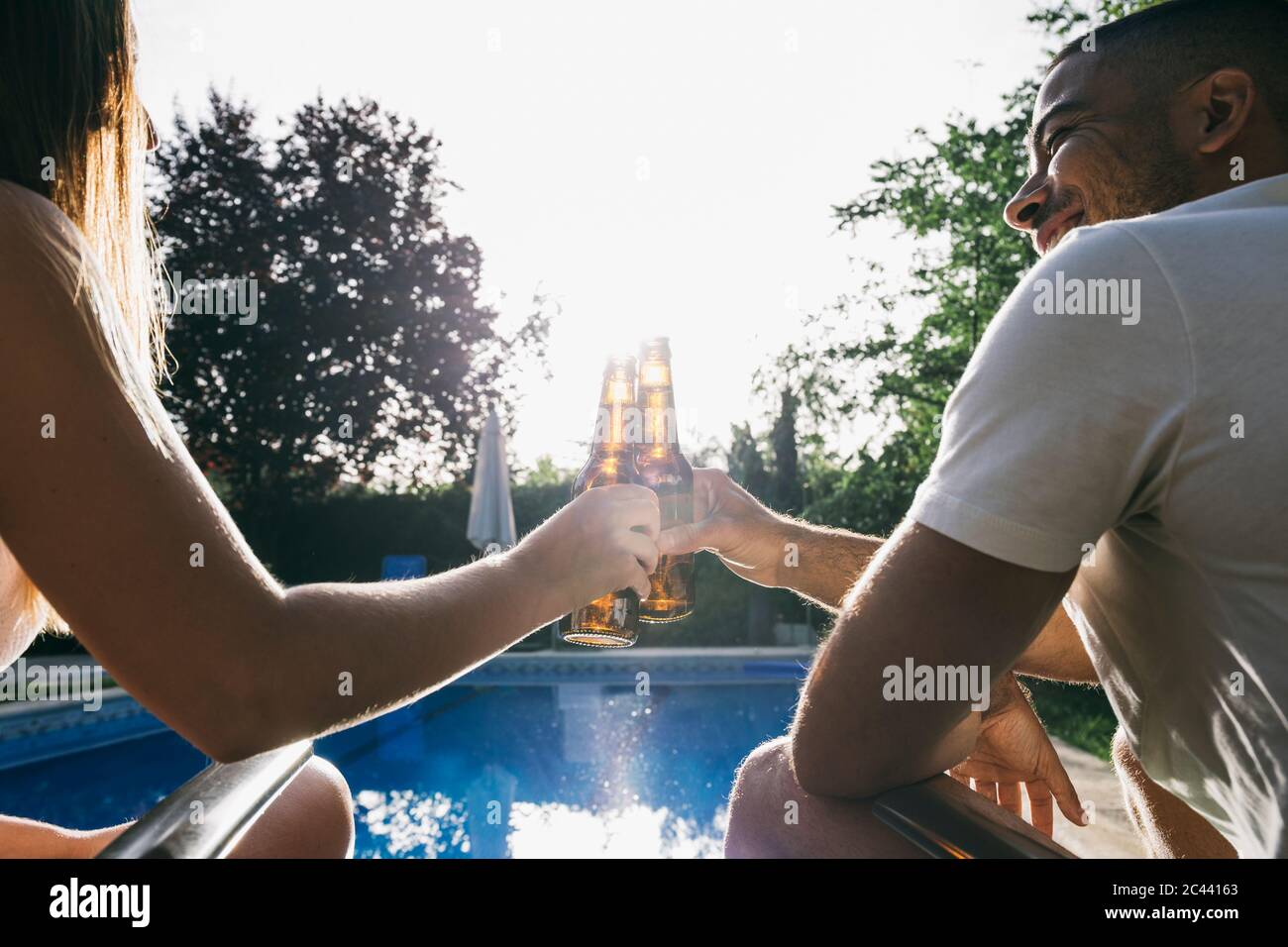 Young couple toasting beer bottle while sitting at poolside Stock Photo