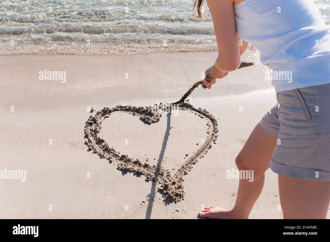 Crop view of woman on the beach  scratching heart in wet sand with wood stick, Sardinia, Italy Stock Photo