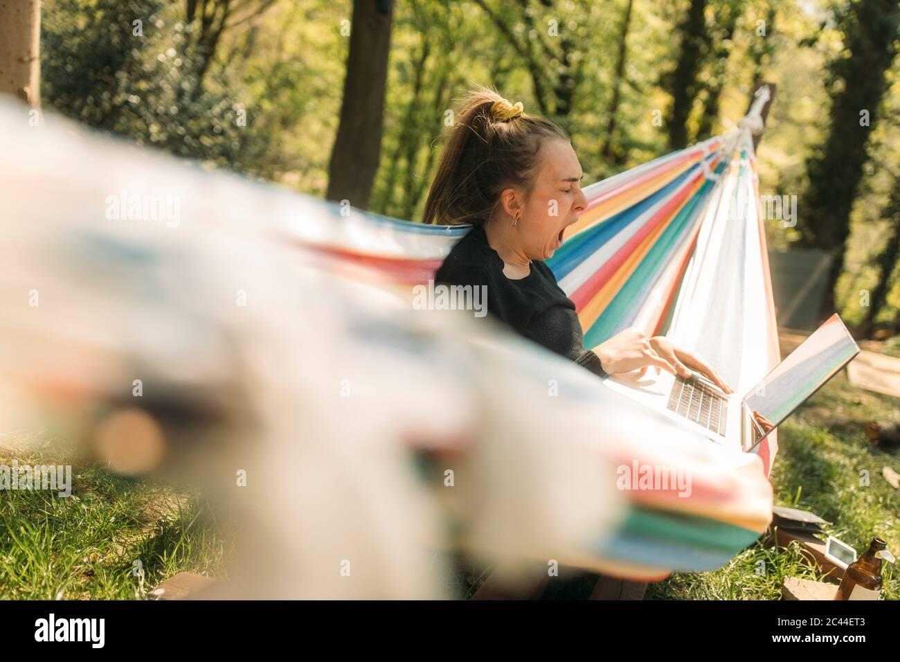 Young woman yawning while using laptop on hammock at yard Stock Photo