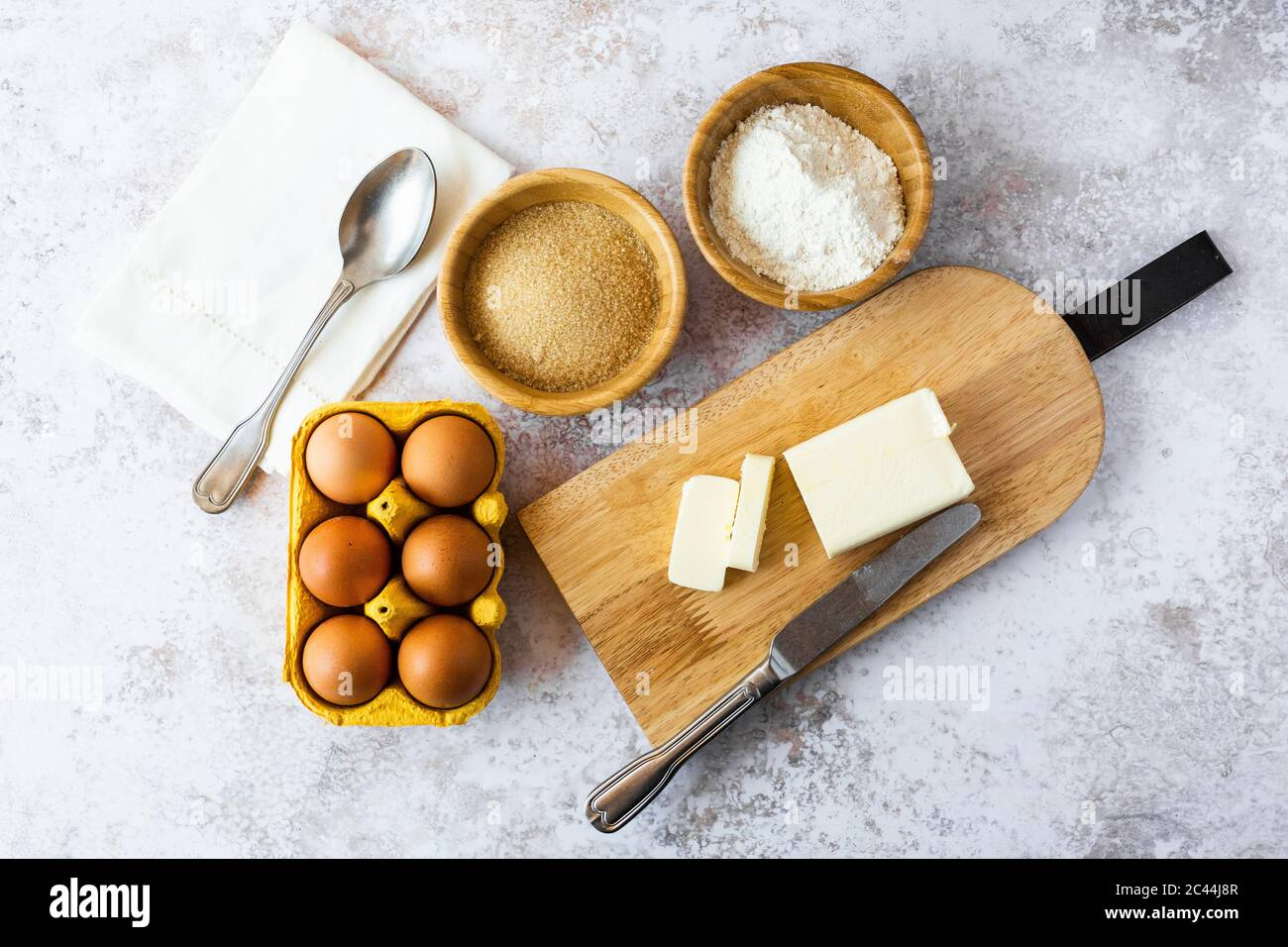 Napkin, spoon, bowls of flour and brown sugar, chicken eggs, cutting board, butter and table knife Stock Photo