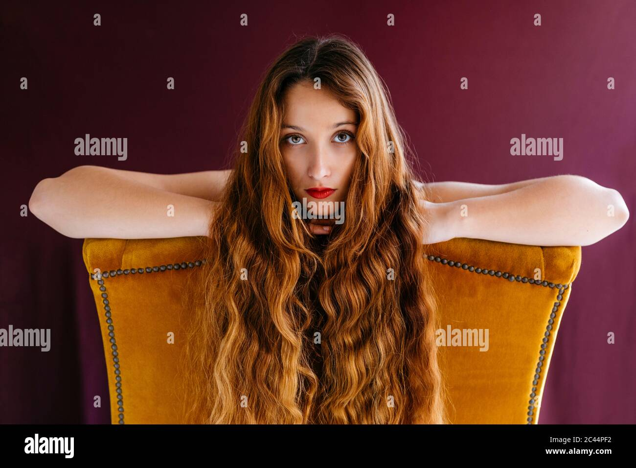Portrait of young female fashion model with long brown wavy hair leaning on golden chair against colored background Stock Photo