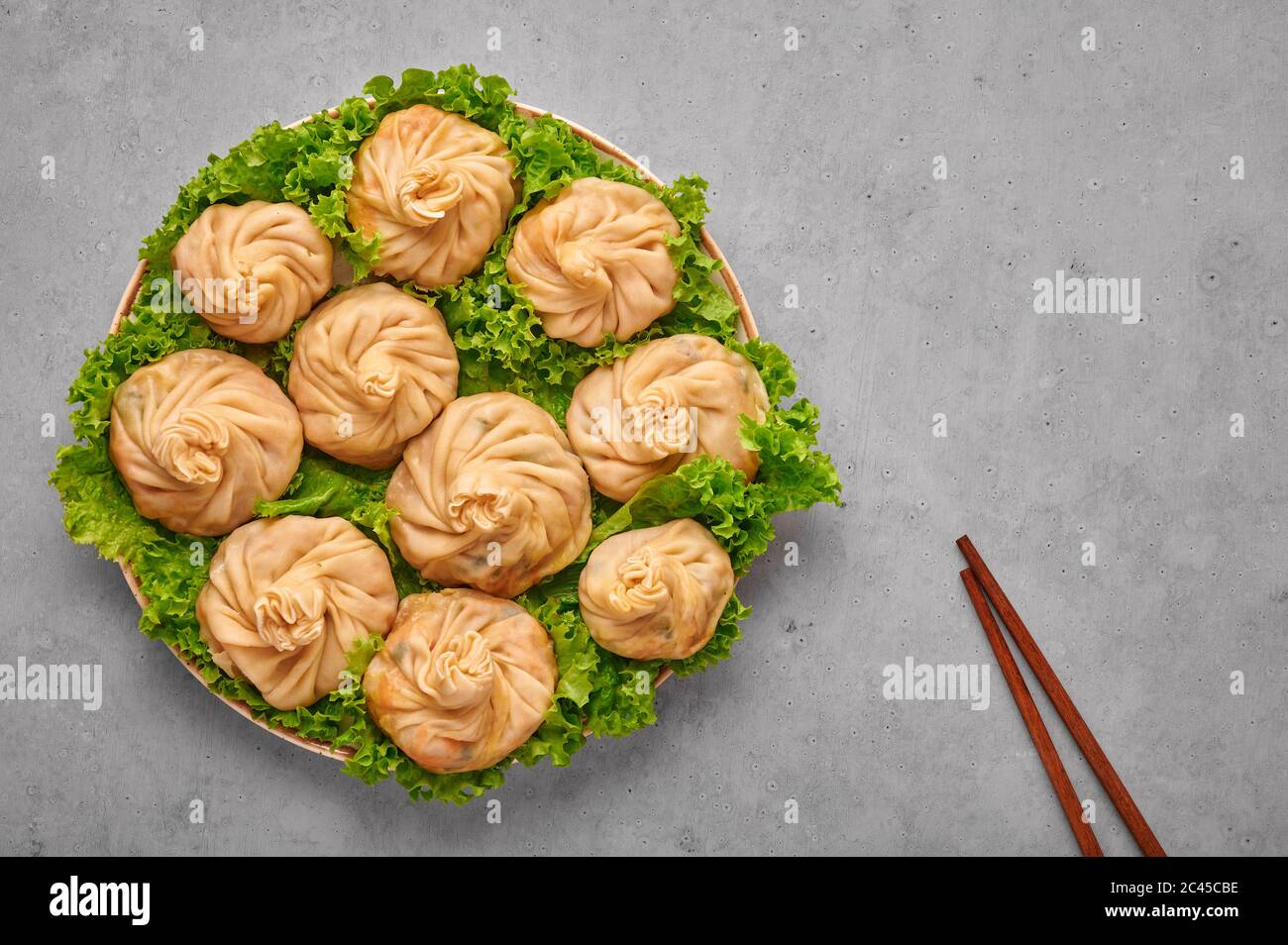 Veg Momos on gray concrete table top . Momos is the popular dish of indian, tibetan, chinese cuisines. Asian food. Vegetarian meal. Copy space. Top vi Stock Photo