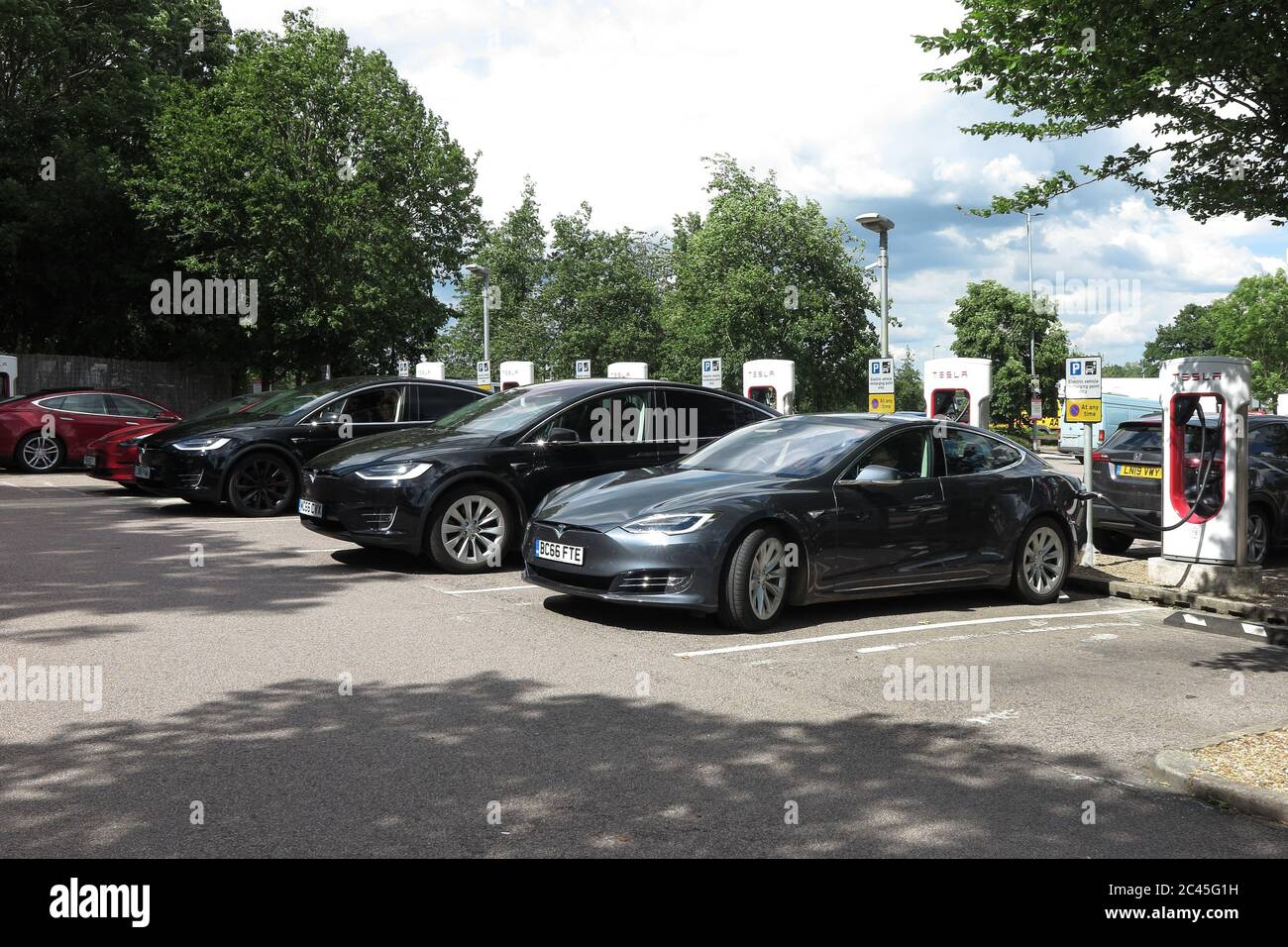 Tesla electric cars charging at South Mimms services, M25 Stock Photo