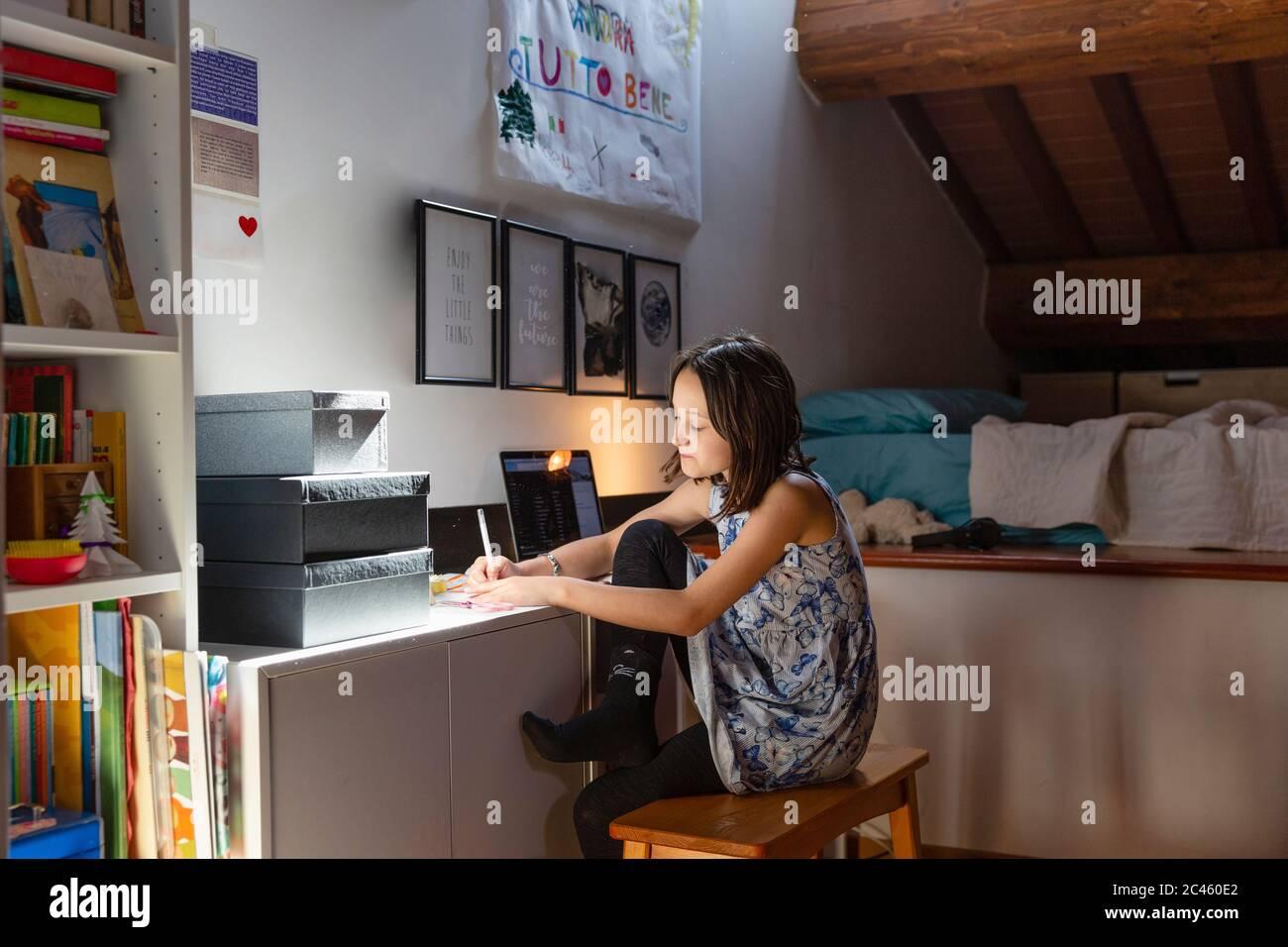 Girl sitting in her bedroom, doing homework during Coronavirus lockdown. Stock Photo