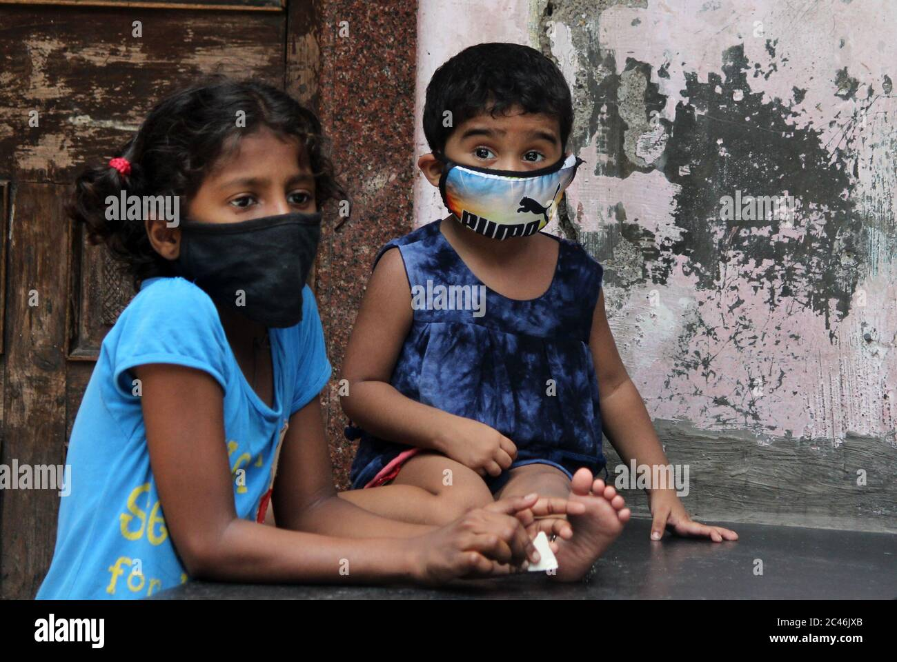 Children wearing protective masks are seen inside a slum colony.The Union Health Ministry on Sunday said the Maharashtra government and the Brihanmumbai Municipal Corporation (BMC) have been able to effectively bring down the covid-19 spread in Dharavi, Asia's largest slum colony. The BMC adopted a model of actively following four T's – Tracing, Tracking, Testing and Treating. An effective containment strategy, conducting comprehensive testing and ensuring uninterrupted supply of goods and essential supplies to the community. Stock Photo