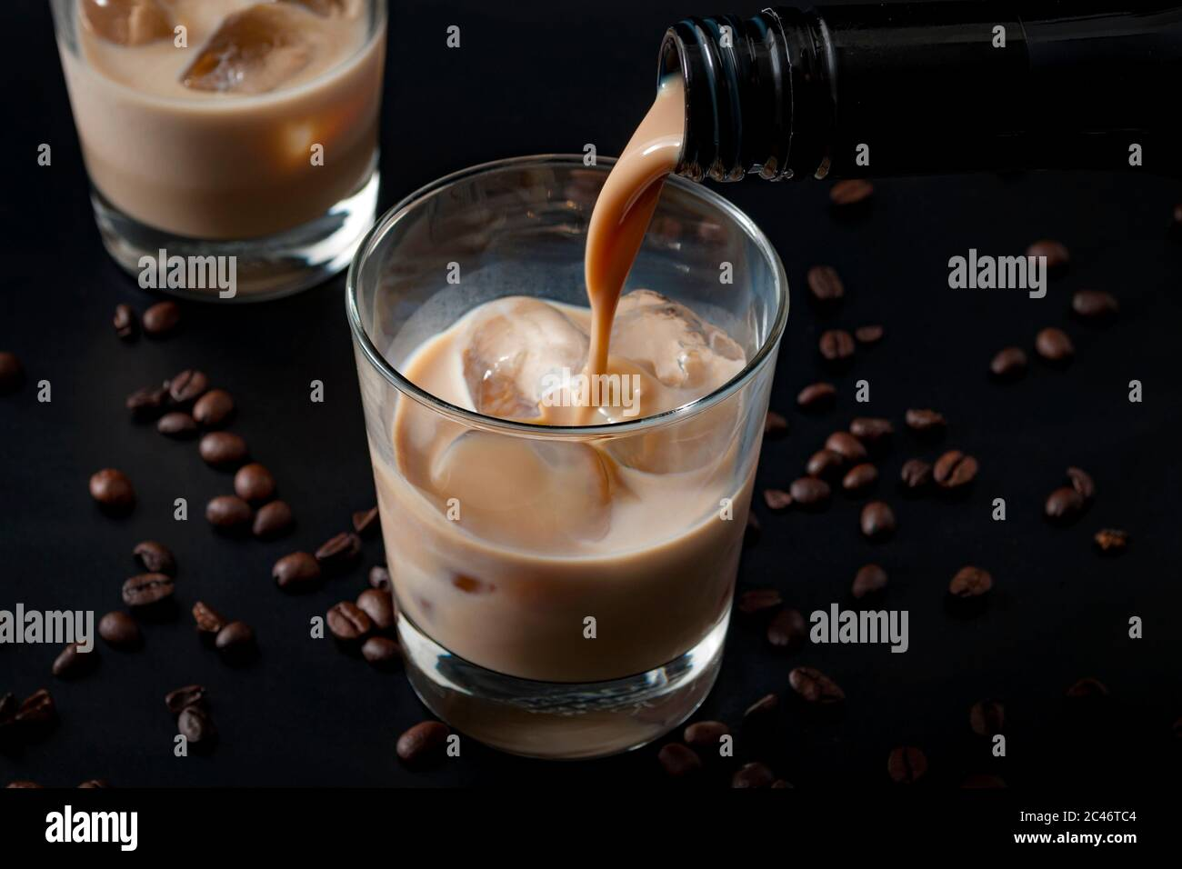 Pouring irish cream in a glass with ice, surrounded by coffee beans on a dark black background Stock Photo