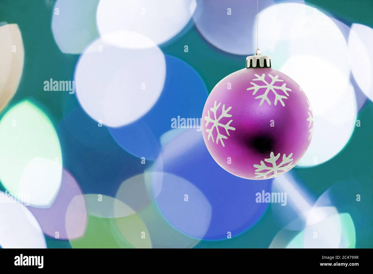 Pink Christmas ball hanging.Lights on the background.Copy space Stock Photo