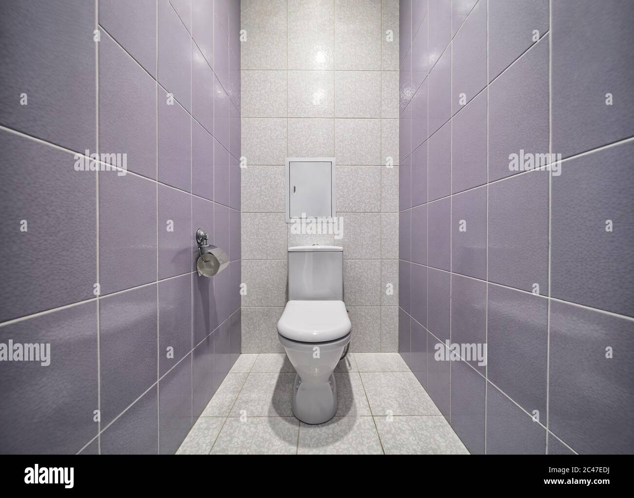 White mounted toilet bowl in modern bathroom with tiled walls and paper holder Stock Photo