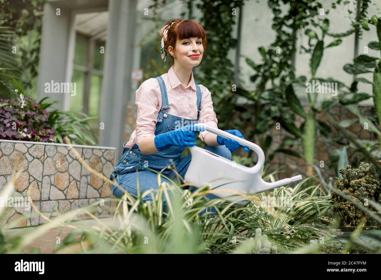 Young beautiful woman in protective gloves and overalls, watering plants in her home garden or in a greenhouse, smiling and looking at the camera Stock Photo