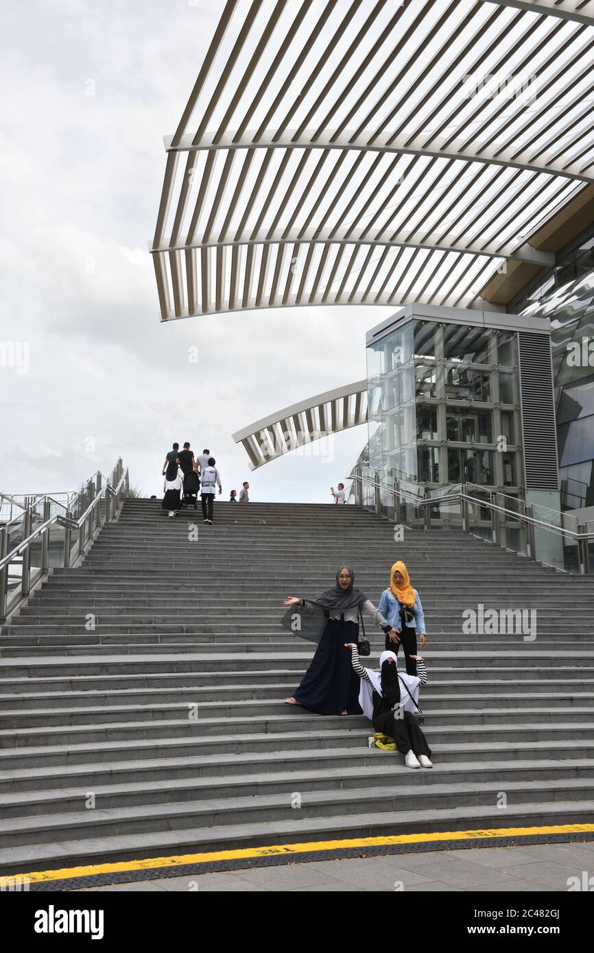 Three young Asian woman with head coverings pose for a friend on the steps at Marina Bay front Shoppes in Singapore, Asia Stock Photo