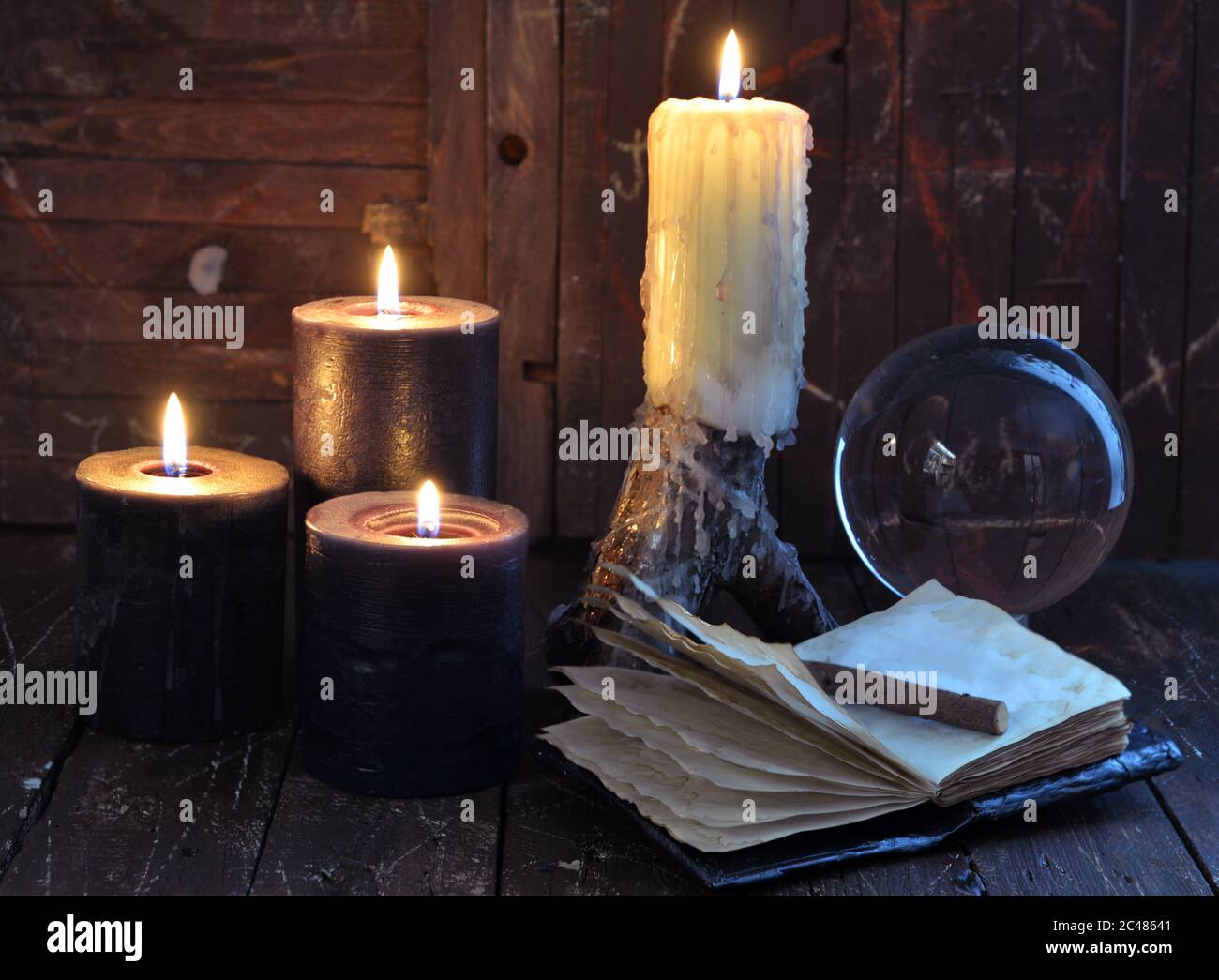 Creepy still life with burning candles, crystal ball and open diary on witch table. Esoteric, wicca and occult background with magic objects, fortune Stock Photo