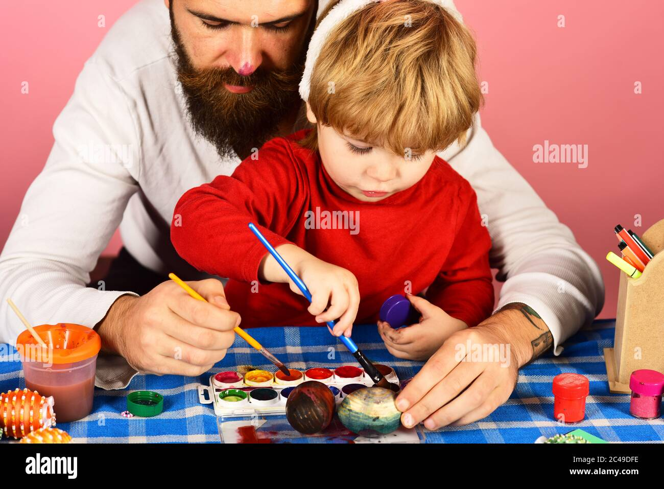 Easter celebration and joy concept. Man with beard and little boy painting eggs for Easter on pink background. Father and son preparing for holiday. Dad with painted nose make decorations Stock Photo