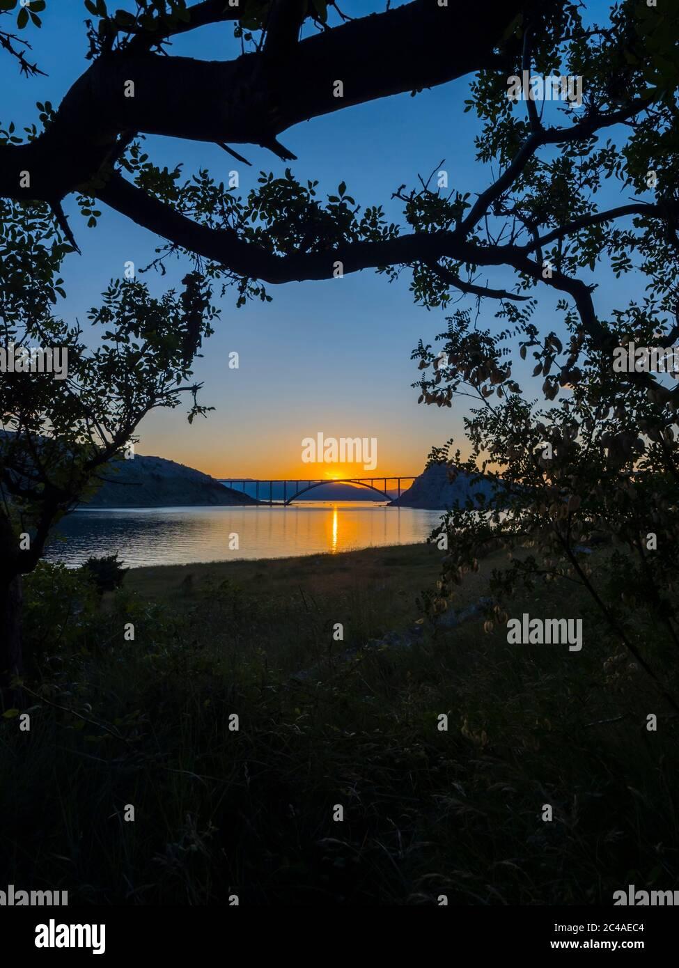 Sunset landscape silhouette silhouetting trees bridge mainland to island Krk Croatia quiet calm calmness Stock Photo