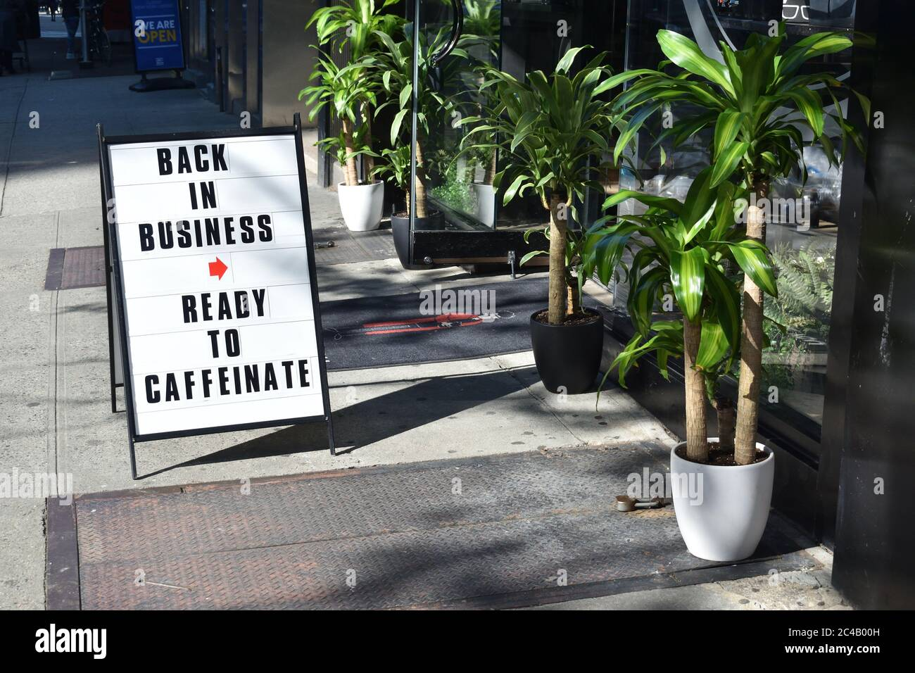 """A-frame sign reading """"Back In Business Ready To Caffeinate"""" on a city sidewalk outside a coffee shop with potted plants, May 7, 2020, in New York. Stock Photo"""