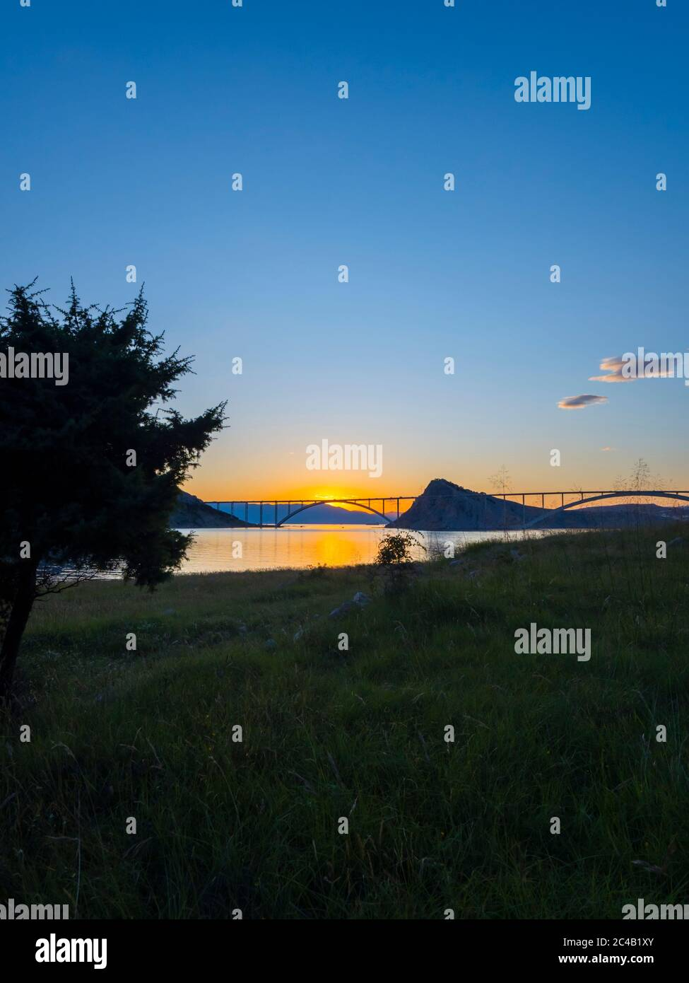 Sunset landscape silhouette silhouetting trees bridge mainland to island Krk Croatia Stock Photo